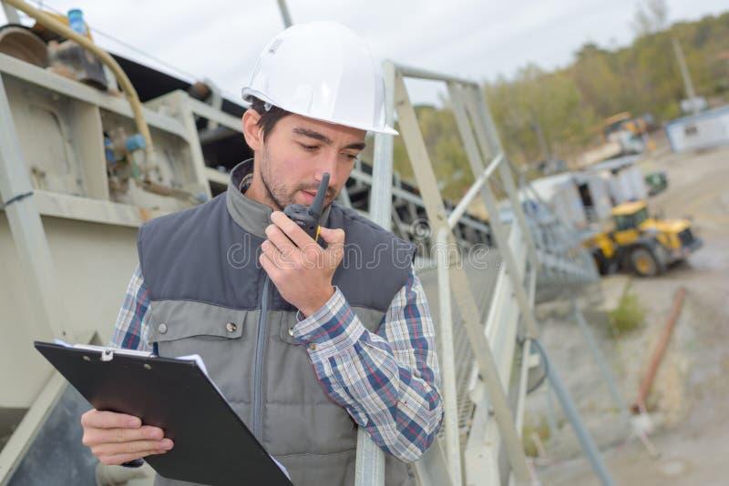 Uomo nel cantiere con la lavagna per appunti ed il walkie-talkie fotografia stock libera da diritti
