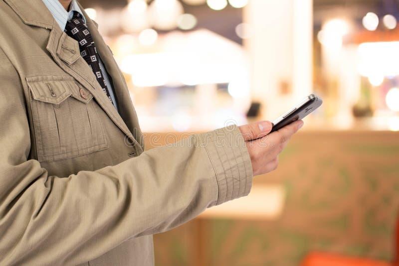 Uomo nel centro commerciale facendo uso del telefono cellulare fotografia stock