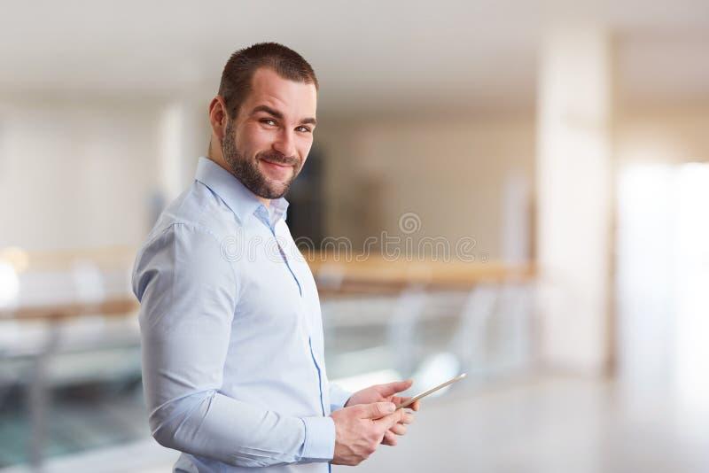 Uomo nel centro di affari con il computer della compressa fotografia stock