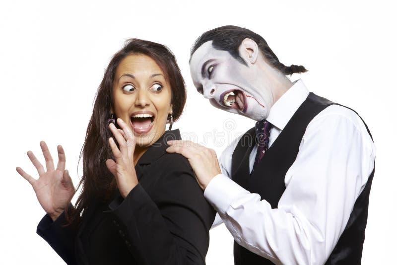 Uomo nel collo mordace delle ragazze del costume del vestito operato da Dracula fotografia stock libera da diritti