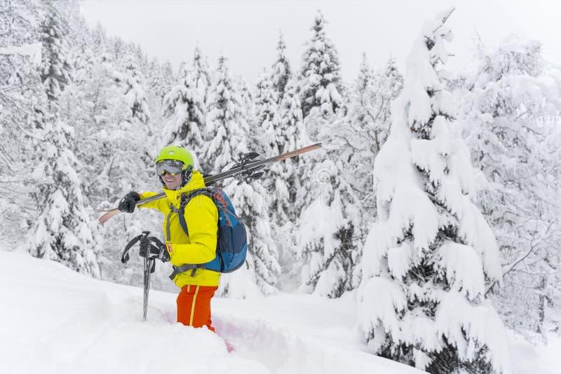 Uomo nel giallo con il soggiorno blu di corsa con gli sci dello zaino con molti abeti intorno e neve polverosa molle Lo sciatore  fotografia stock