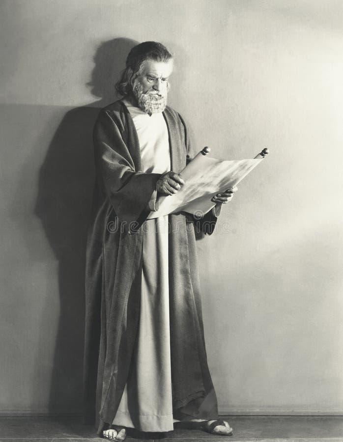 Uomo nel rotolo della lettura dell'abito fotografie stock libere da diritti