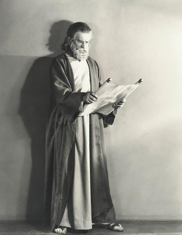 Uomo nel rotolo della lettura dell'abito fotografia stock