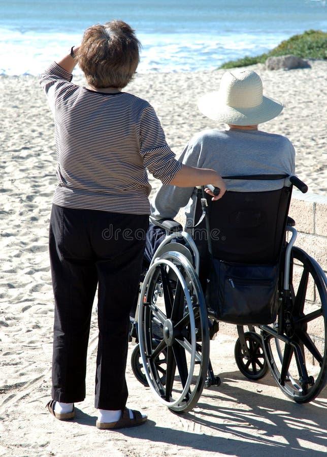Uomo nel wheelcheair alla spiaggia immagini stock