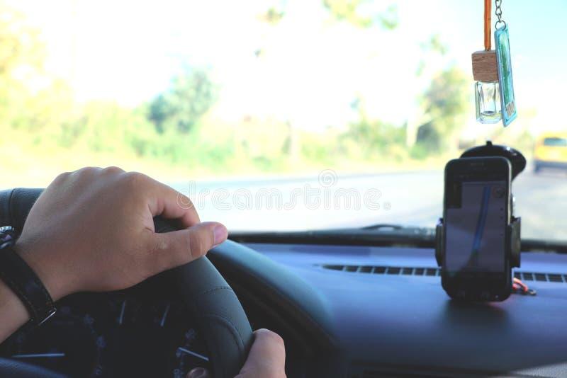 Uomo nell'automobile e nella tenuta del telefono cellulare nero con navigazione dei gps della mappa, tonificata al tramonto fotografia stock libera da diritti