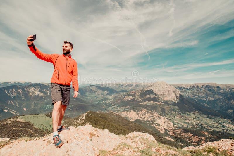 Uomo nell'escursione dell'ingranaggio che prende un selfie fuori fotografie stock libere da diritti