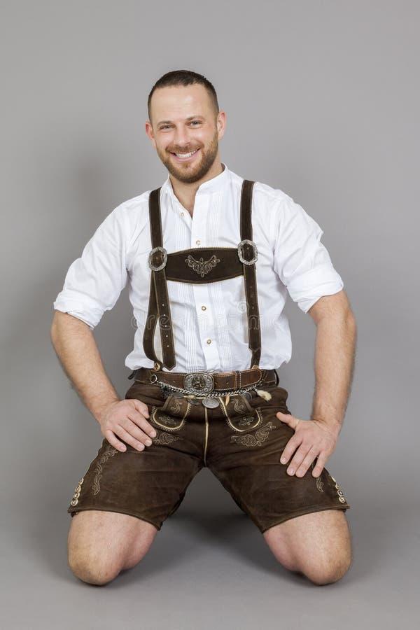 Uomo nell'inginocchiamento tradizionale bavarese dei lederhosen immagini stock