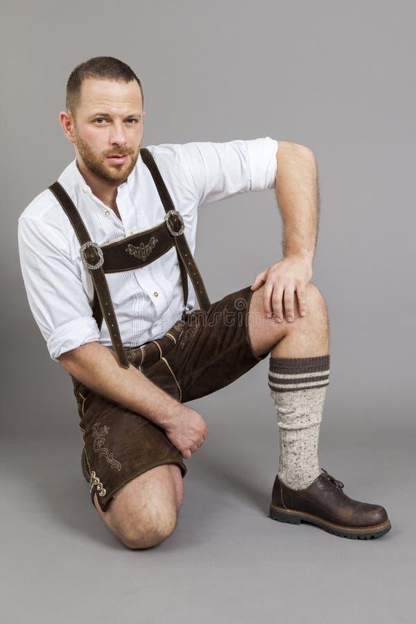 Uomo nell'inginocchiamento tradizionale bavarese dei lederhosen fotografia stock