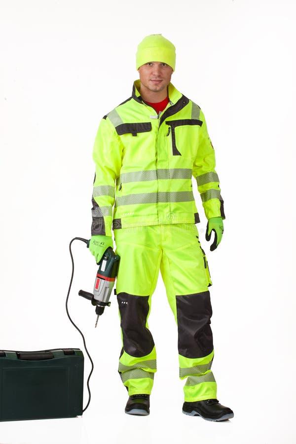 Uomo nell'uniforme con il trapano elettrico immagine stock libera da diritti