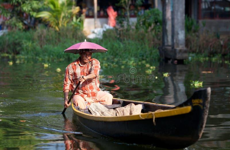 Uomo nella barca di legno negli stagni del Kerala fotografie stock