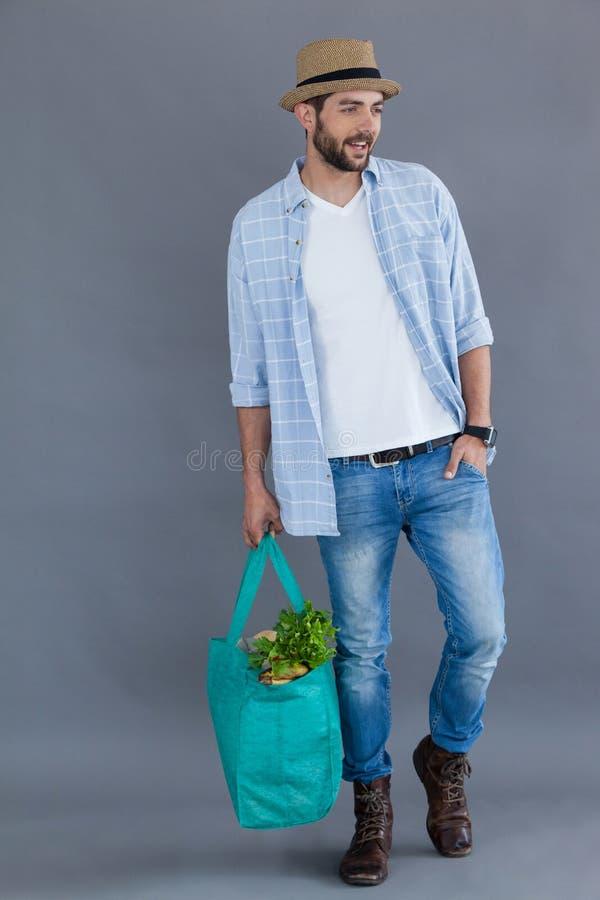 Uomo nella borsa di drogheria della tenuta del cappello della fedora fotografie stock