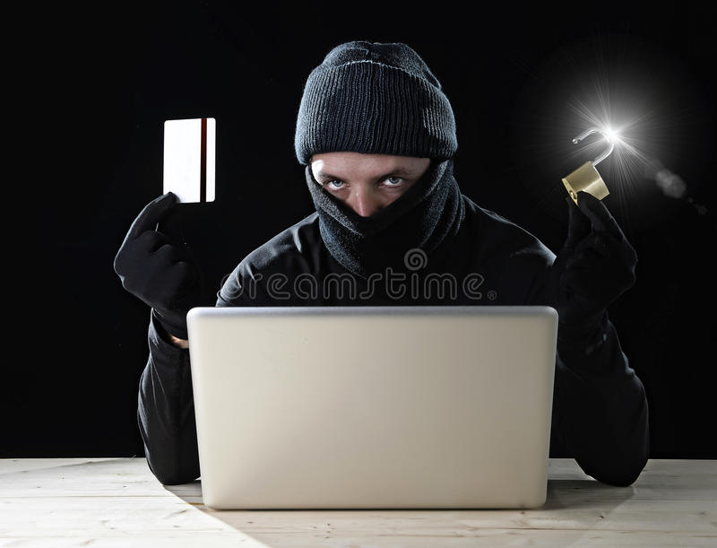 Uomo nella carta di credito nera della tenuta e serratura facendo uso del computer portatile del computer per attività criminale  fotografia stock libera da diritti