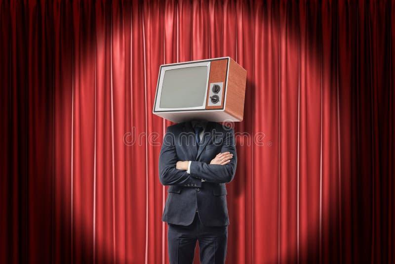Uomo nella condizione del vestito con le armi piegate, con la testa del set televisivo invece, in riflettore vicino alla tenda ro immagini stock