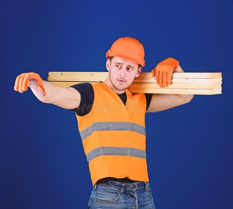 Uomo nella direzione indicante del casco, del casco e dei guanti protettivi, fondo blu Carpentiere, falegname, forte costruttore immagine stock