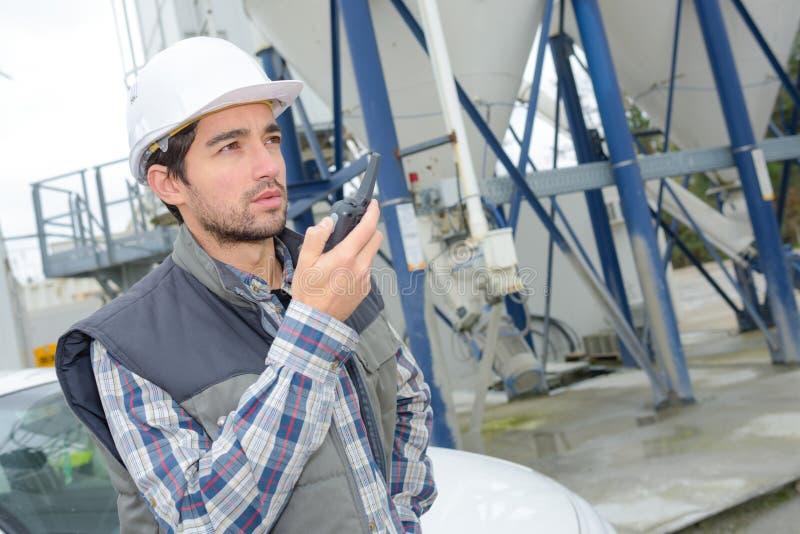 Uomo nella fabbrica del cemento facendo uso del walkie-talkie fotografie stock