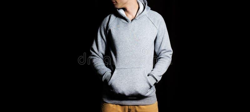 Uomo nella maglia con cappuccio grigia in bianco, maglietta felpata su un fondo nero, derisione su, spazio libero immagine stock