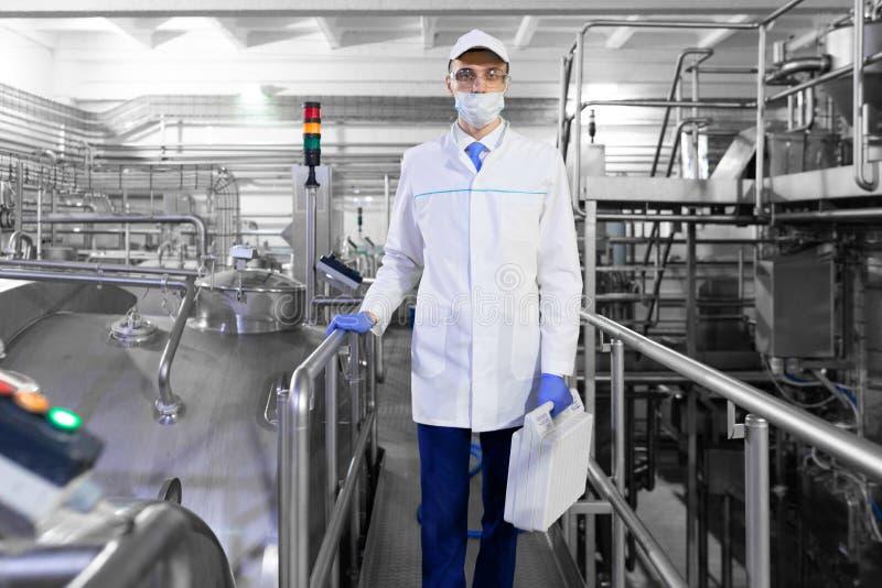 Uomo nella maschera ed abito con una cartella a disposizione che sta sui prodotti lattier-caseario della fabbrica fotografia stock