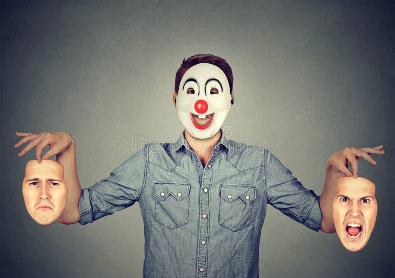 Uomo nella maschera felice del pagliaccio che tiene due fronti che esprimono rabbia e tristezza immagini stock libere da diritti