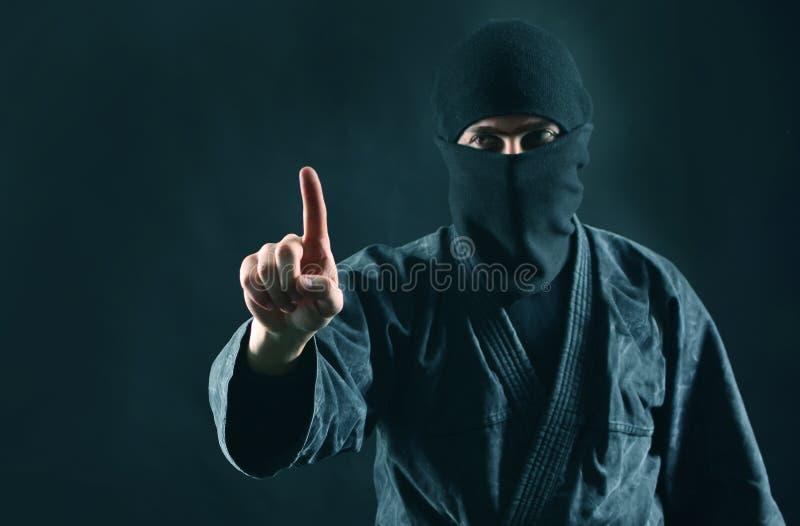 Uomo nella maschera nera con indicare dito su fotografie stock libere da diritti