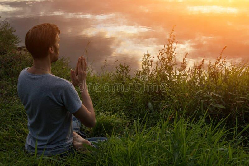 Uomo nella meditazione di posa del loto, preghiera al sole immagine stock