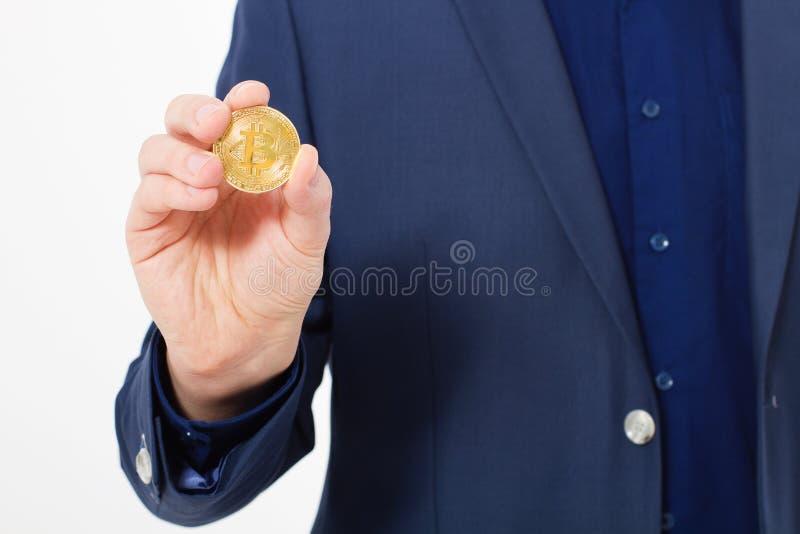 Uomo nella moneta del bitcoin dell'oro della tenuta del vestito isolata su fondo bianco Copi lo spazio e derida su Fuoco selettiv fotografia stock libera da diritti