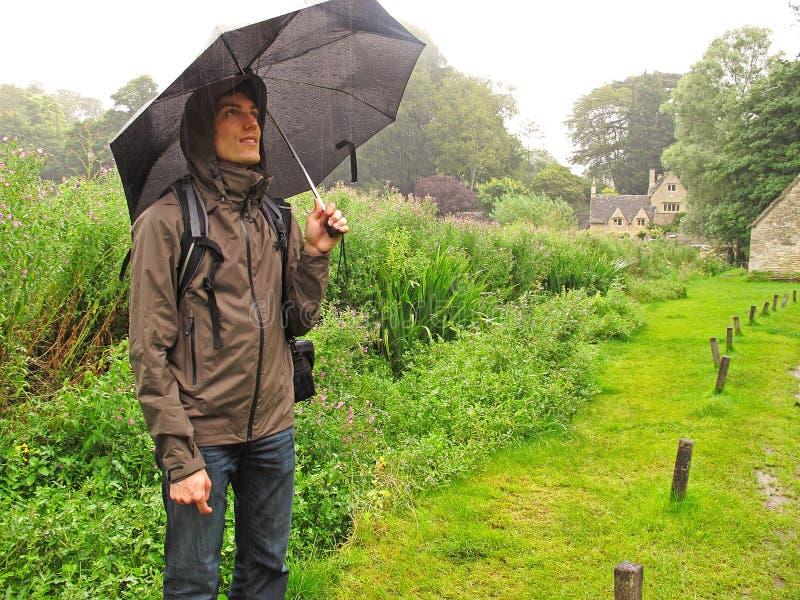 Uomo nella pioggia con l'ombrello fotografia stock