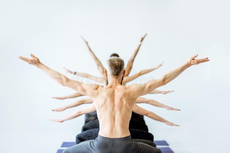 Uomo nella posa di yoga con le armi multiple sui precedenti immagine stock