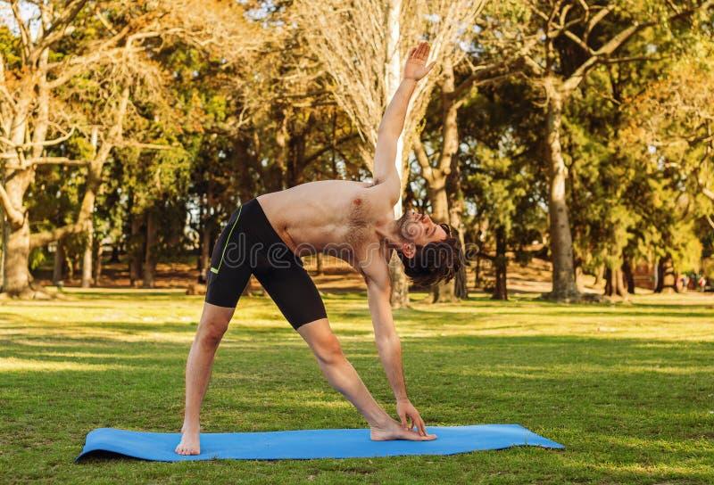 Uomo nella posizione di yoga nel parco fotografia stock