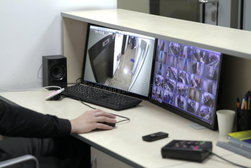 Uomo nella sala di controllo che controlla il metraggio multiplo del Cctv fotografia stock libera da diritti