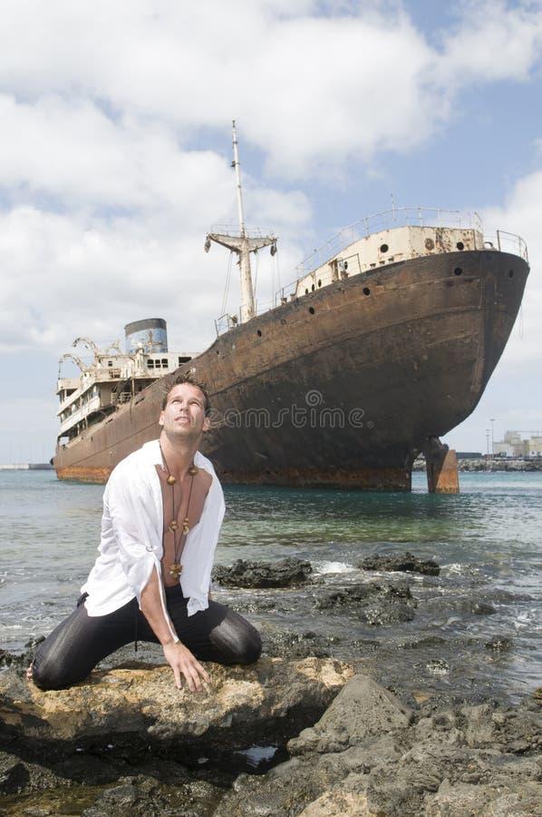 Uomo nella spiaggia con la nave abbandonata fotografia stock