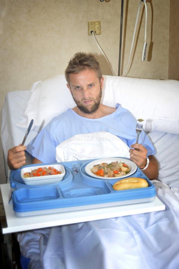 Uomo nella stanza di ospedale che mangia l'alimento della clinica di dieta sana nell'espressione lunatica del fronte di ribaltame fotografia stock
