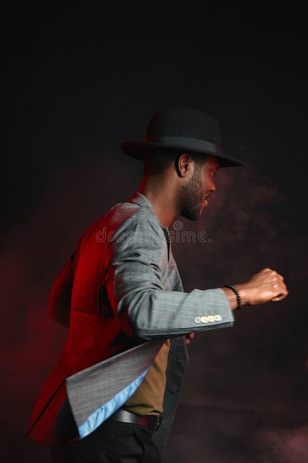 Uomo nero del jazzista che porta vestito alla moda e cappello grigio nel moto immagini stock