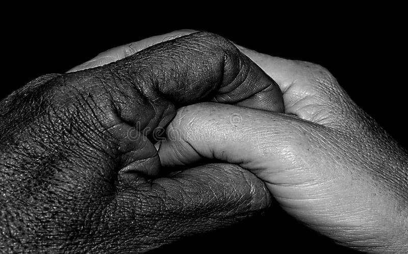 Uomo nero, donna bianca che stringe le mani fotografia stock libera da diritti