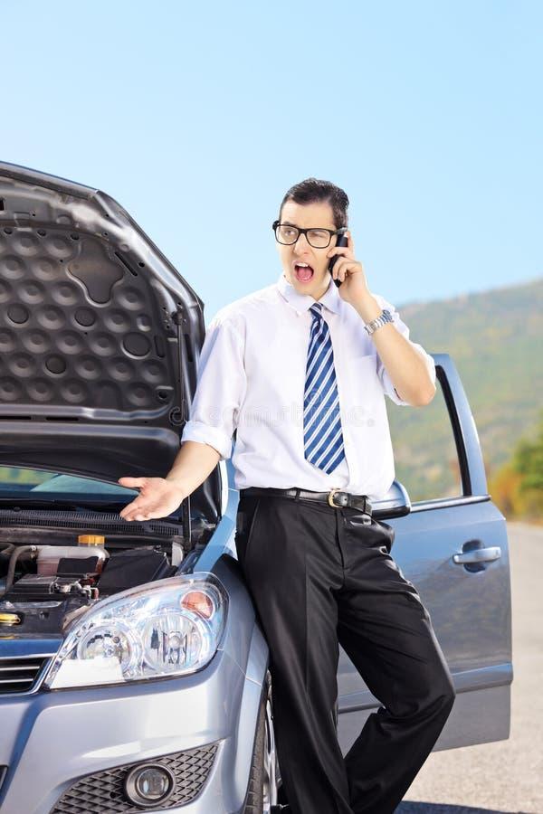 Uomo nervoso che sta accanto alla sua automobile rotta e che parla su un pho fotografie stock libere da diritti