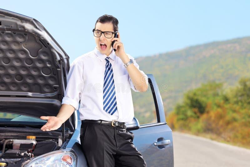 Uomo nervoso che sta accanto alla sua automobile rotta e che parla su un pho immagini stock