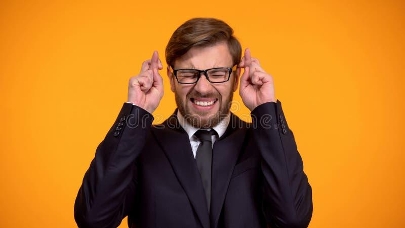 Uomo nervoso in dita d'attraversamento del vestito per buona fortuna, speranti di vincere immagine stock libera da diritti