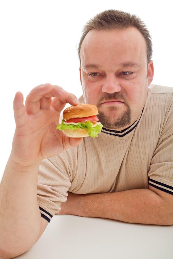 Uomo non felice circa il suo hamburger fotografie stock