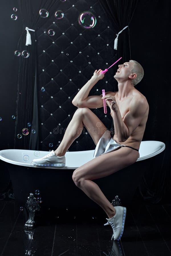 Uomo nudo che si siede sull'orlo del bagno fotografia stock
