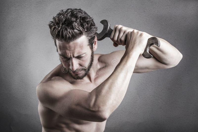 Uomo nudo del petto che per mezzo di una chiave o di una chiave come arma fotografie stock