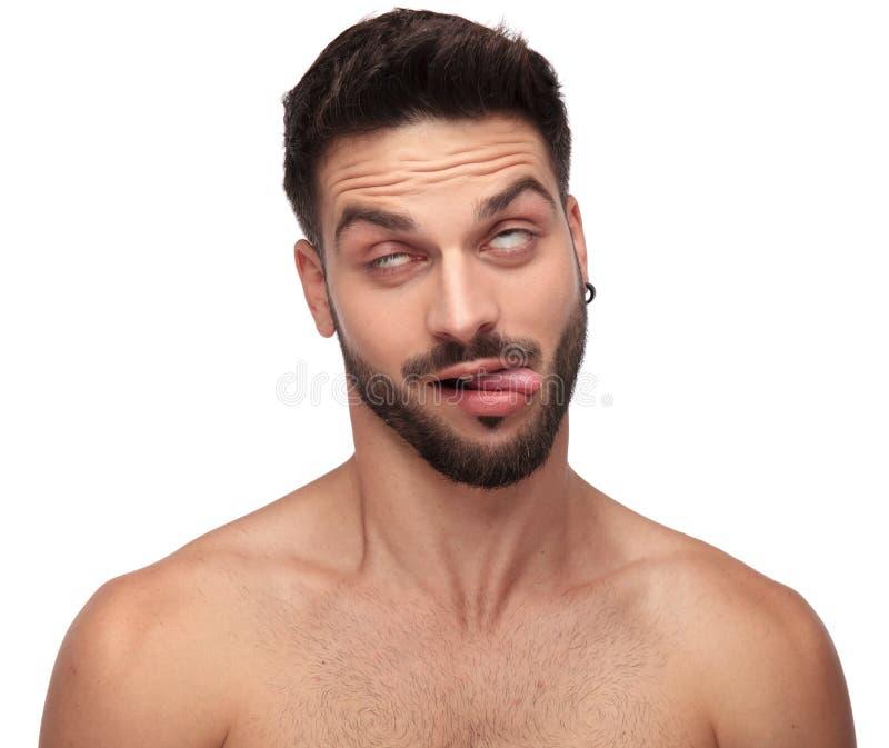 Uomo nudo sciocco che imbroglia intorno rotolamento dei suoi occhi, esponenti lingua fotografia stock