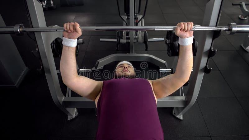Uomo obeso che alza bilanciere, piano personale di allenamento della palestra, desiderio di essere forte fotografia stock