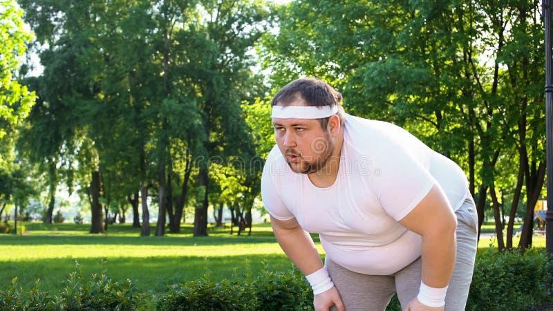 Uomo obeso che corre all'aperto, dal respiro, sormontando pigrizia ed insicurezza fotografie stock libere da diritti