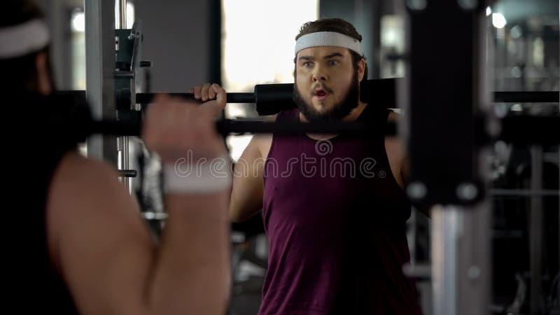 Uomo obeso che fa esercizio con il bilanciere nella palestra di sport, desiderio di essere forte ed esile fotografia stock