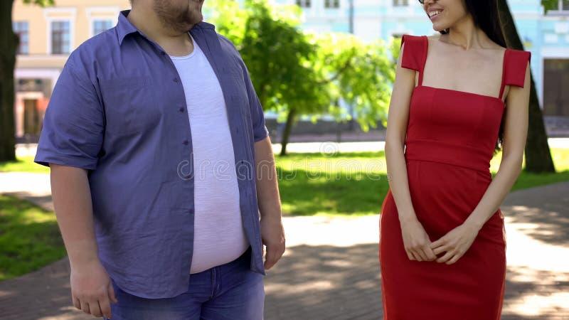 Uomo obeso che flirta con bella signora elegante, bellezza interna nella priorità immagini stock libere da diritti
