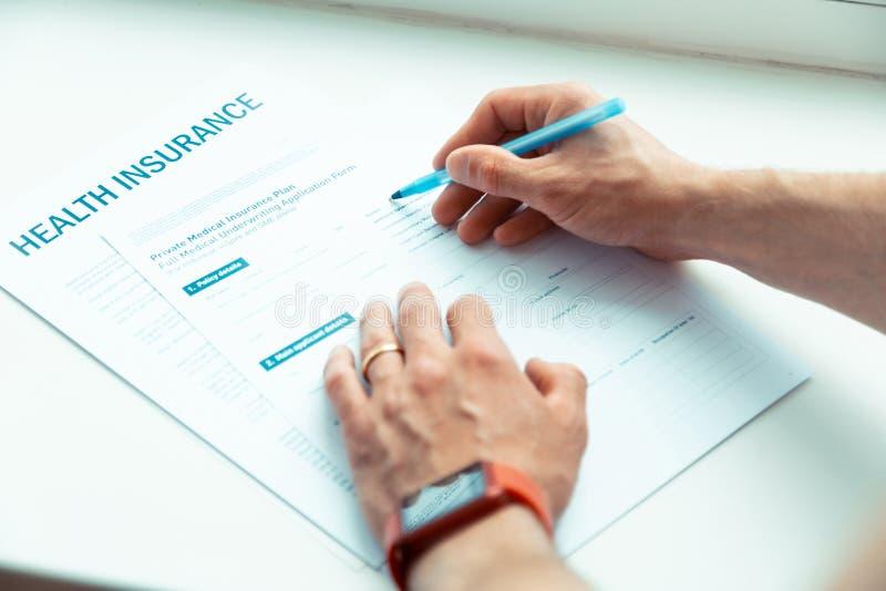 Uomo in occhiali che firma i documenti che compra assicurazione-malattia fotografia stock libera da diritti