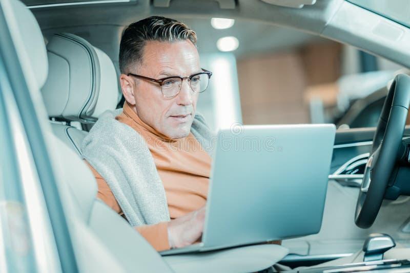 Uomo occupato che lavora al parcheggio dell'automobile immagine stock libera da diritti