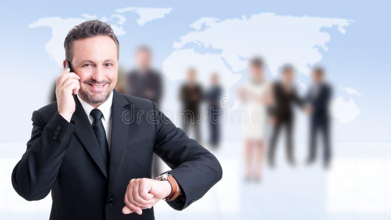 Uomo occupato di affari che per mezzo del telefono e controllando tempo fotografie stock libere da diritti