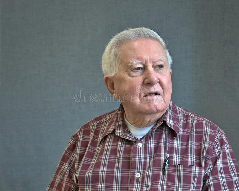 Uomo ottuagenario senior in plaid con fondo grigio fotografia stock libera da diritti