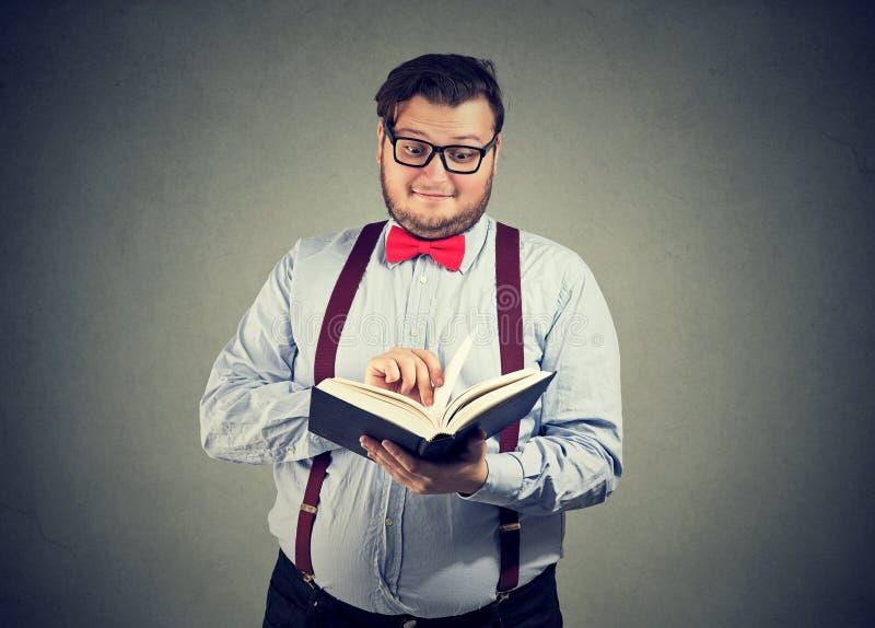 Uomo paffuto sorpreso che gode del libro fotografie stock libere da diritti