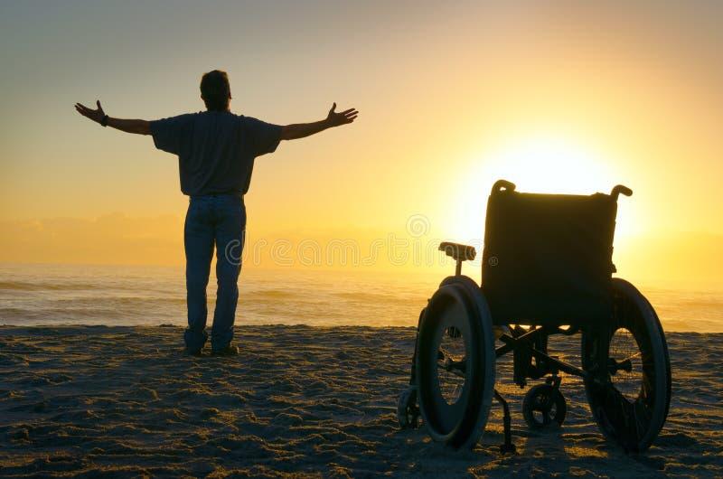 Uomo paralizzato guarente spirituale di miracolo che cammina alla spiaggia al sunri fotografie stock